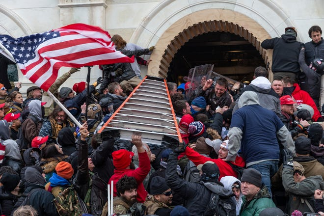 Insurrectionists clashing with police use a ladder to try to force entry into the Capitol on Jan. 6 in Washington, D.C. Rioters broke windows and breached the Capitol in an attempt to overthrow the results of the 2020 election.