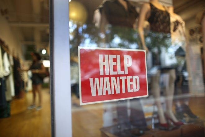 MIAMI -- A help wanted sign is seen in the window of the Unika store.