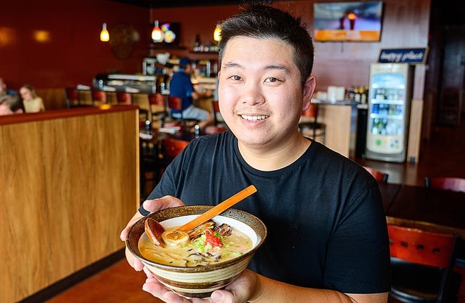 Ginger Bistro owner and chef Tuna Liu holds a bowl of Pork Tonkotsu Ramen noodles in the dining room of his restaurant in St. Augustine on Tuesday.