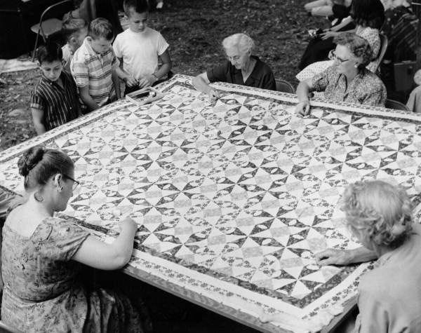 Hand-stitching a quilt around the frame