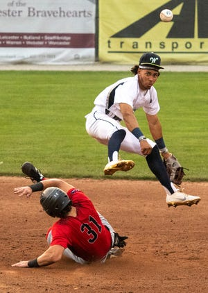 Worcester's Randy Flores watches his throw to first as he leaps over the sliding Will MacLean of Nashua in the fourth inning Tuesday night.