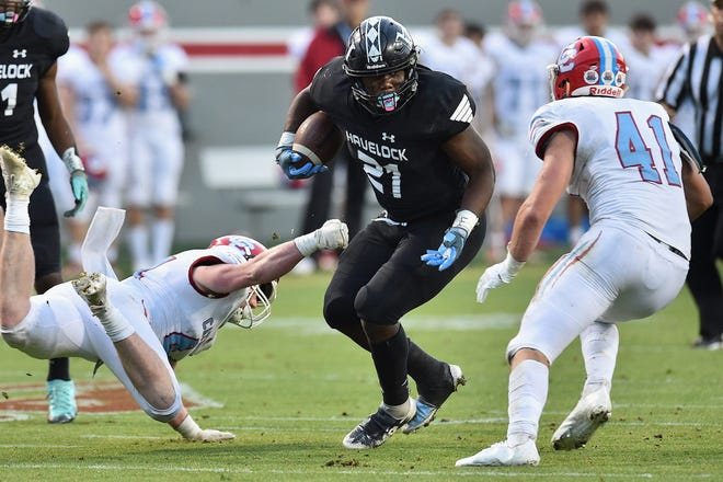 Havelock's Kamarro Edmonds (21) looks for an opening against Charlotte Catholic's Connor Daugherty (41) and Liam Barbee (44) during the first half of the NCHSAA 3A football championship game at N.C. State's Carter-Finley Stadium in Raleigh on May 7, 2021.