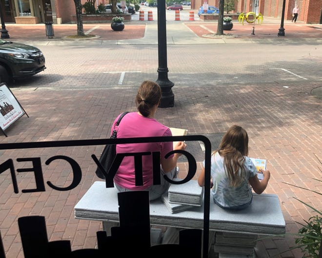 A mother and daughter read while seated on the new sculpture and bench outside City Center Gallery & Books in downtown Fayetteville on Wednesday morning.