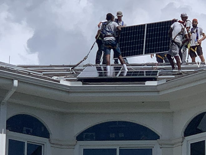 Workers atop a building at the Oak Hammock retirement community install solar panels Tuesday morning.