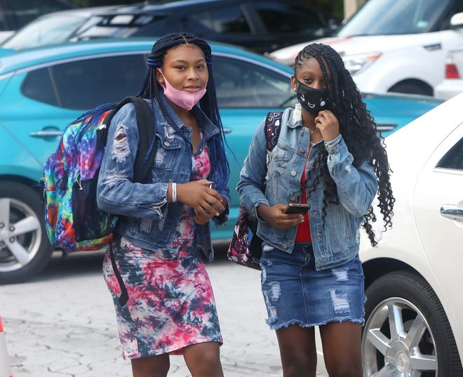 Students adjust their masks before walking into Fort Clarke Middle School on the first day of school in August 2020. After earlier announcing that schools would not mandate masks when the school year begins Aug. 10, Alachua County School Board members now must wrestle with what sort of rules to impose, if any.