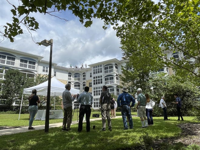 Onlookers watch the installation of solar panels atop a building at Oak Hammock Tuesday.