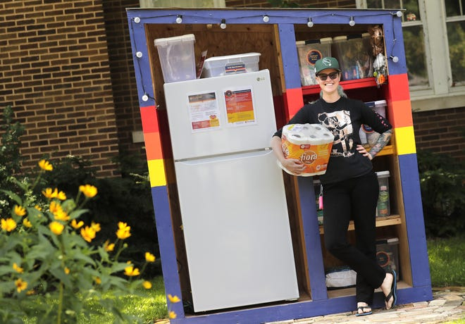 Tj Hobbs, founder and director of Hope Fridge, holds paper goods in front of the Neenah community fridge at 428 Ninth St.