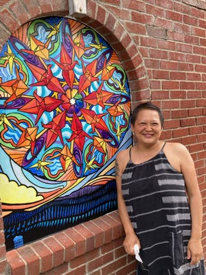 Lara Nguyen stands before one of her eight murals Madison Arts Council is planning to place around downtown Marshall.