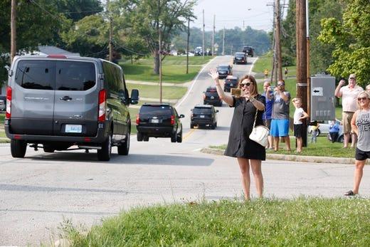 People watch President Joe Biden's motorcade on his way to Mount Saint Joseph University on Thursday, July 21, 2021.