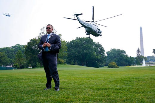 A secret service agent gets blown by the wind as Marine One, with President Joe Biden on board, lifts off from the South Lawn of the White House in Washington, Wednesday, July 21, 2021. Biden is traveling to Cincinnati to push his economic policies. (AP Photo/Susan Walsh)