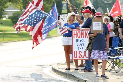 Donald Trump supporters line the street across from Mount Saint Joseph University in Delhi Township, a Cincinnati suburb, where President Joe Biden will participate in a CNN town hall Wednesday, June 14, 2021.