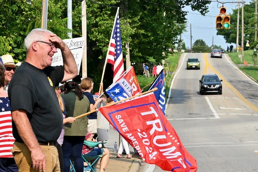 Supporters of former President Donald Trump stand on the corner of Delhi Road and Neeb Road to protest the arrival of President Joe Biden outside of Mount Saint Joseph University, where Biden is set to speak at a town hall on Thursday, July 21, 2021, in Delhi.