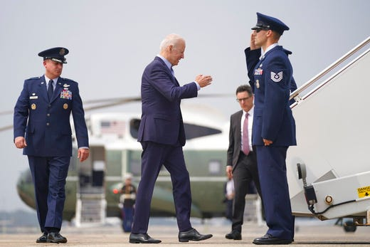 President Joe Biden boards Air Force One at Andrews Air Force Base, Md., Wednesday, July 21, 2021, to travel to Cincinnati for a town hall and to tour an electrical training center, as Col. Matthew E. Jones, Commander of the 89th Airlift Wing, left, watches. (AP Photo/Andrew Harnik)