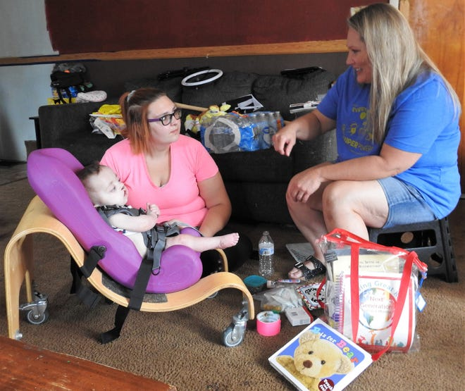 Tisha King, right, of Help Me Grow speaks with Sara Chittum and her 9-month-old daughter, Zia, during a recent home visit. The program currently has about 30 families in Coshocton it helps with children up to age 3 in developing basic skills.