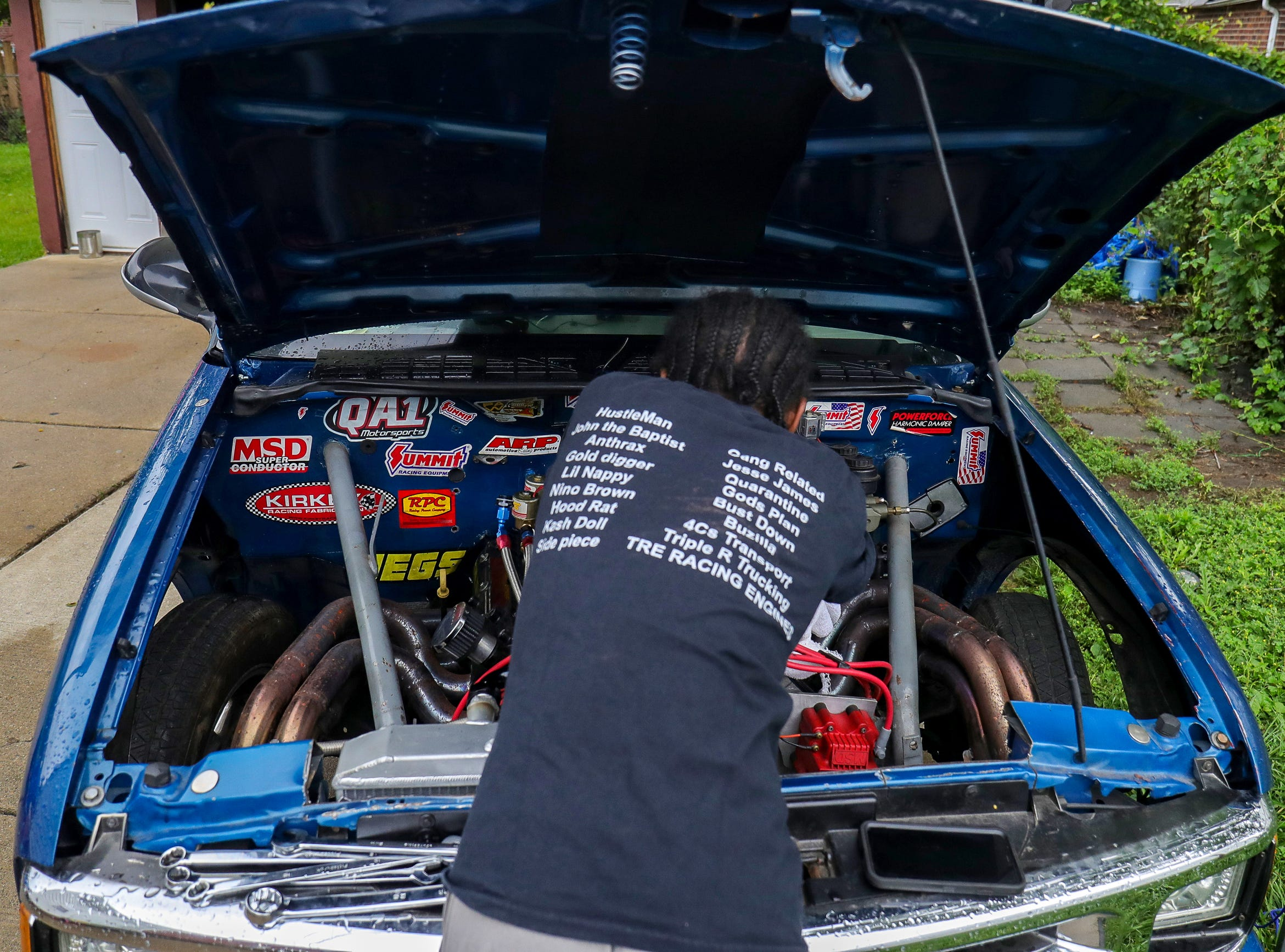 """Joemari Fox, 21, works on his 1997 Chevrolet S-10 in the backyard of his Eastpointe home ah he gets the car he named """"Payroll"""", ready for an event sponsored by Payso Productions at Lapeer International Dragway on Tuesday, July 13, 2021."""