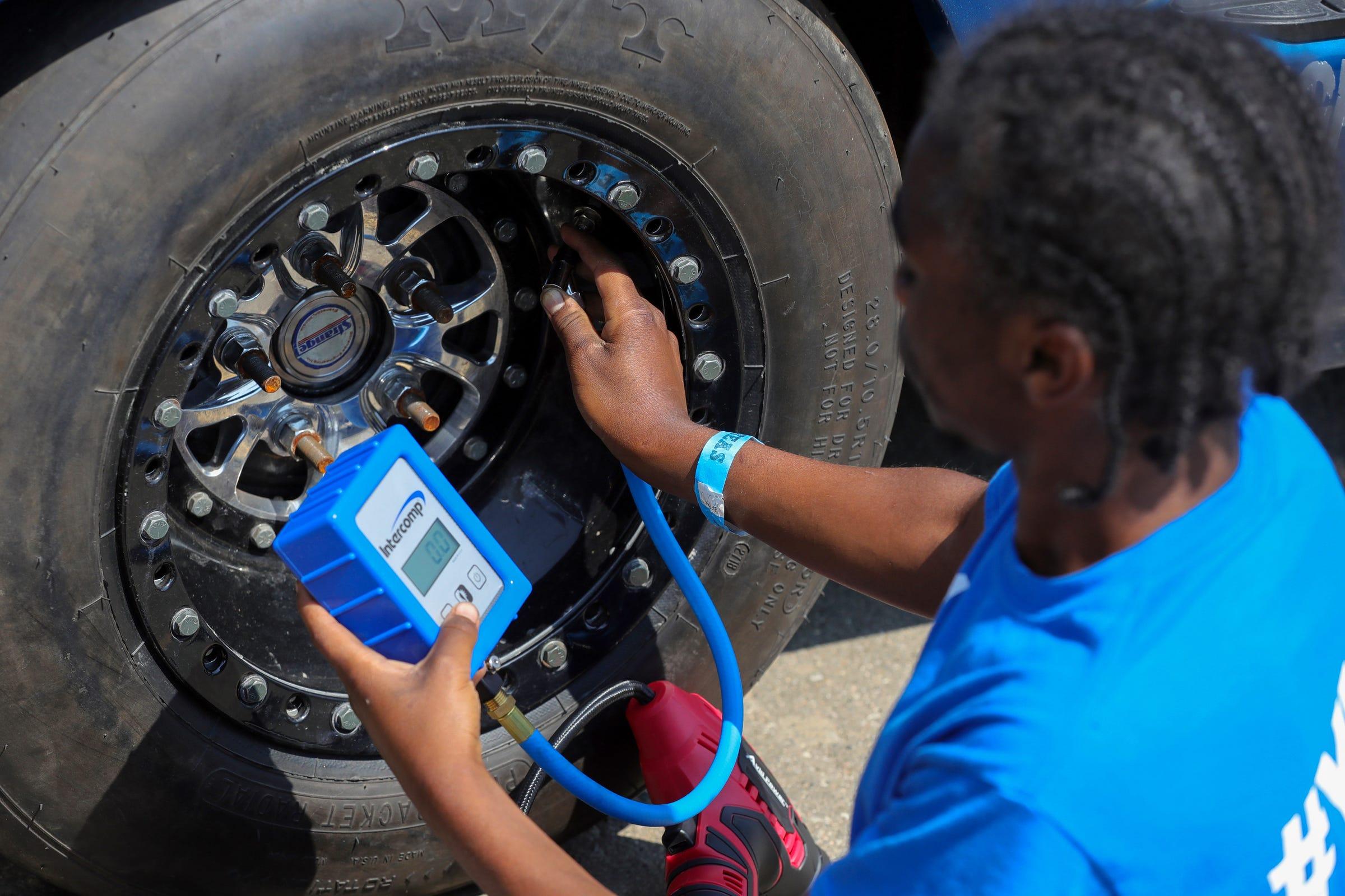 "Joemari Fox, 21, checks the tires on ""Payroll"" in the pits before racing at Lapeer International Dragway on Saturday, July 17, 2021."