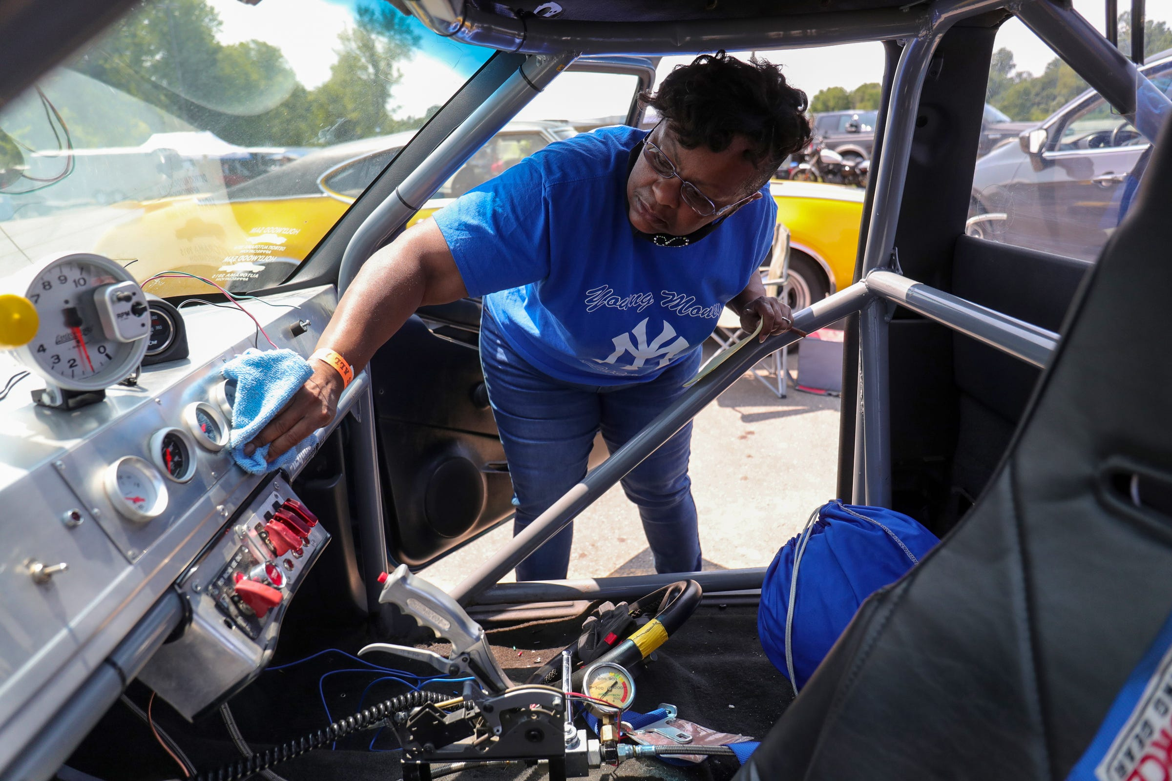 """Gail Fox Wilson wipes down the interior of her son Joemari Fox's car """"Payroll"""" ahead of his race at Lapeer International Dragway on Saturday, July 17, 2021. Gail and other family members helped prepare Joemari's car in the pits."""