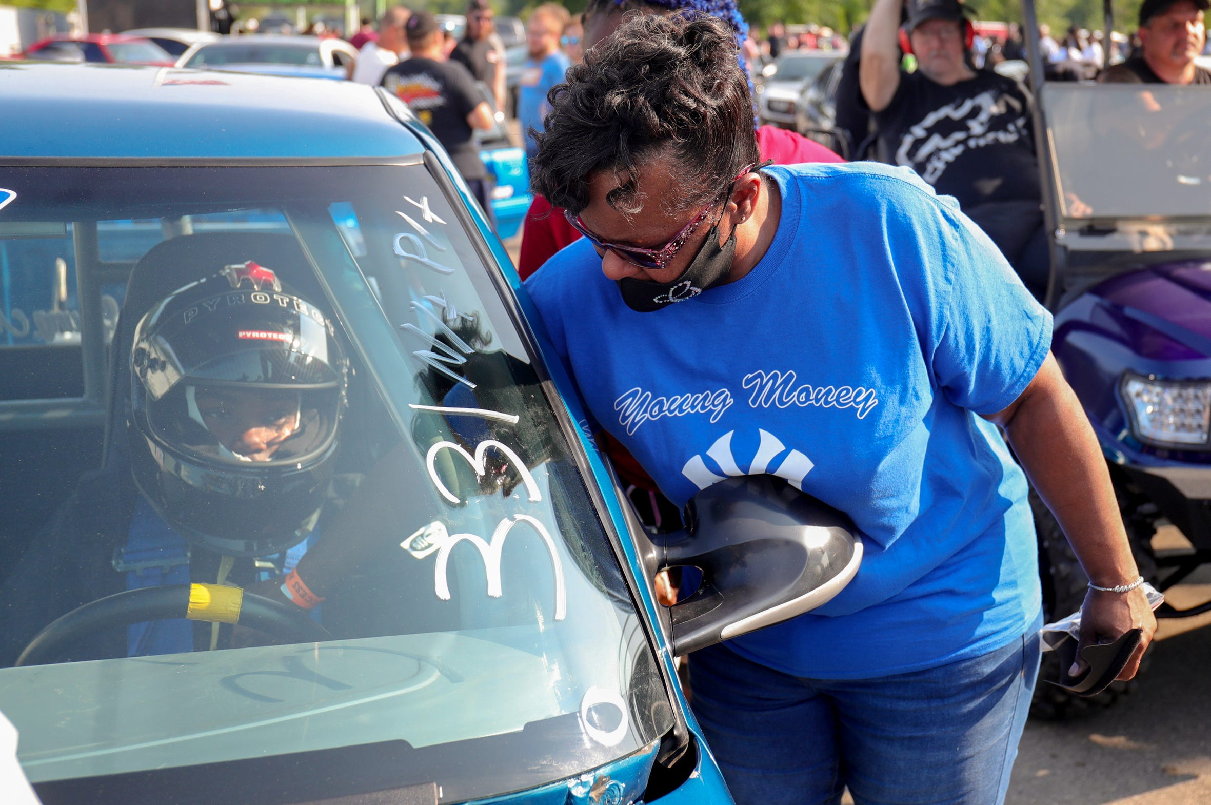 """Gail Fox Wilson checks to make sure her son Joemari Fox, 21, is strapped securely into his car """"Payroll"""" before his pass at Lapeer International Dragway Saturday, July 17, 2021. Gail pulled on his seatbelts several times before the race saying, """"it helps me stay calm knowing I have checked to see Joemari is safely strapped in before he races""""."""