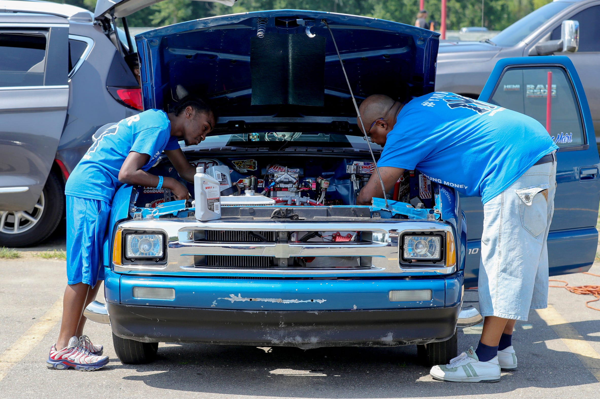 """Joemari Fox, 21, and his dad, Stafford Wilson, put oil in Fox's car, """"Payroll,"""" in the pits before racing in an event sponsored by Payso Productions at Lapeer International Dragway on Saturday, July 17, 2021."""