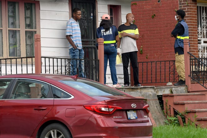 FEMA employees Lauren Graham, second from left, and Jaquor Faison, far right, talk with homeowners who were affected by recent severe storms and flooding in Detroit.