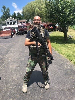Barry Croft of Delaware holds a tactical shotgun in a photo used during his Jan. 13, 2021 bond hearing for his alleged involvement in the attempted kidnapping of Gov. Gretchen Whitmer.