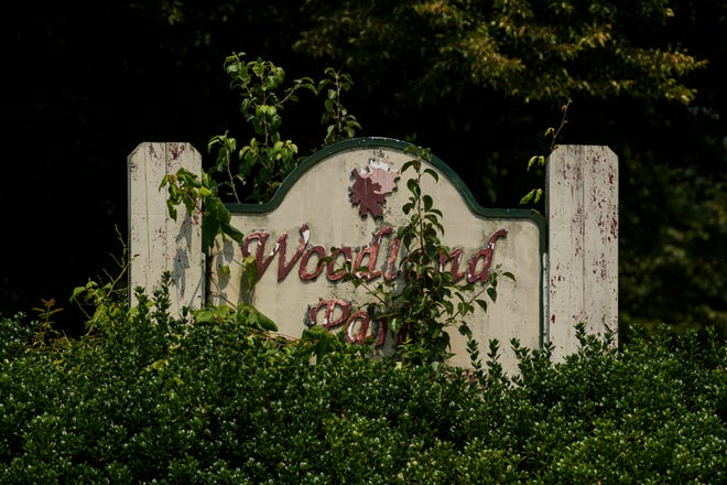 An overgrowth of bushes cover a sign at Woodland Park Apartments on Evansville's South Side, Wednesday, July 21, 2021.