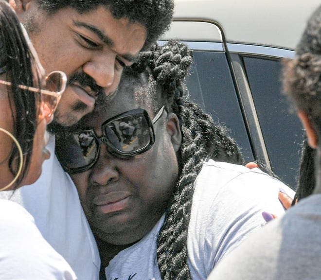 Shadavia Rosemond, right, mother of a 1-year-old boy who died after choking at the Bumble Bee Daycare and Learning Center in Greenville, gets a hug from her cousin Travis Ballenger of Greer, at a press conference across the street from the business on Wednesday.