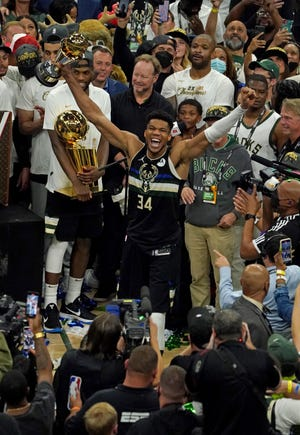 Milwaukee Bucks forward Giannis Antetokounmpo (34) holds his FINALS MVP Trophy as Milwaukee Bucks forward Khris Middleton (22) holds Larry O'Brien NBA Championship Trophy after the Bucks won Game 6 of the NBA Finals at Fiserv Forum in Milwaukee on Tuesday, July 20, 2021.