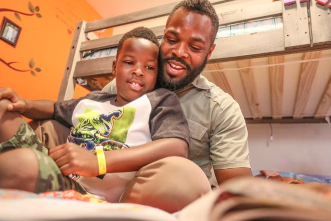 """AJ and his father Adriel Sr. read """"My Daddy Doesn't Need a Cape,"""" by Sheryl Smiley-Oliphant. """"I feel happy when I read with my dad,"""" AJ said. """"I smile because I love my daddy."""""""