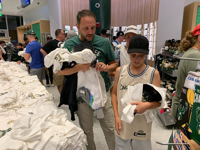 Danny Rosenthal, left, with his son CY, 12, from Washington D.C. shop at the Bucks Pro Shop at Fiserv Forum after the Milwaukee Bucks won the NBA championship on Tuesday, July 20, 2021 against the Phoenix Suns at the Fiserv Forum.