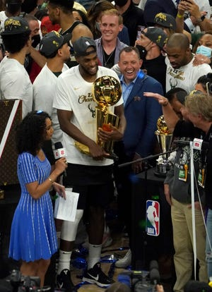 Bucks general manager Jon Horst and forward Khris Middleton hold Larry O'Brien trophy after the Bucks the championship in Game 6 of the NBA Finals on July 20.