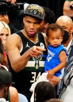 Bucks forward Giannis Antetokounmpo with his son Liam after winning an NBA title, Milwaukee's first in 50 years.