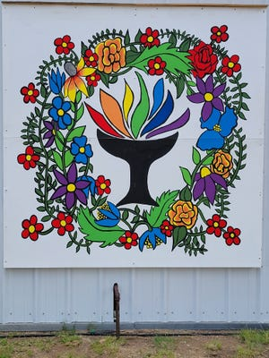 The mural, eight by eight feet, features a flaming Chalice, a long-time symbol of the faith surrounded by flowers.
