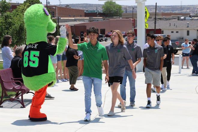 Carson Padilla of the Farmington Sting gives Connie Mack World Series mascot Mack a high-five on July 21 as the team arrives at the Farmington Civic Center.