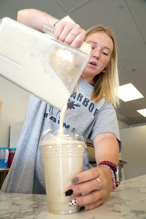 Milford Nutrition owner Jenna Beers pours a moose tracks shake for a customer on July 21, 2021.
