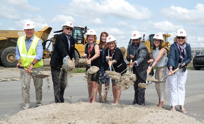 Livonia Mayor Maureen Brosnan-Miller, fifth from left, Wayne County Executive Warren Evans, second from left, and others toss some dirt at the groundbreaking for the Ashley Capital Livonia West Commerce Center on Amrhein in Livonia on July 21, 2021.