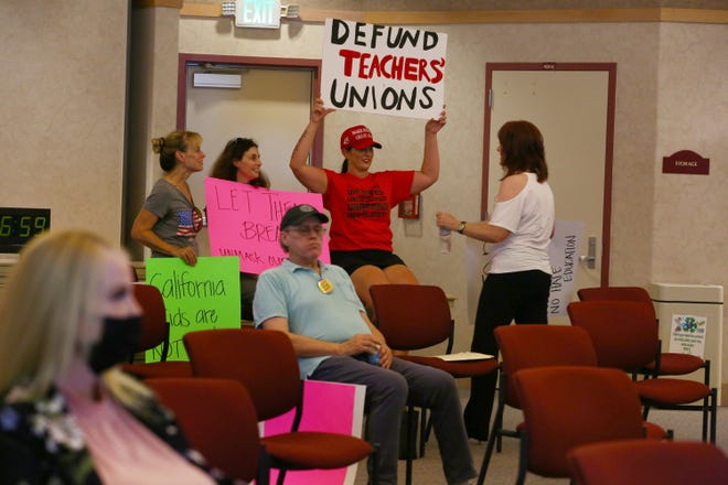 People hold signs prior to the Desert Sands Unified School District's regular board meeting in La Quinta, Calif., on July 20, 2021.