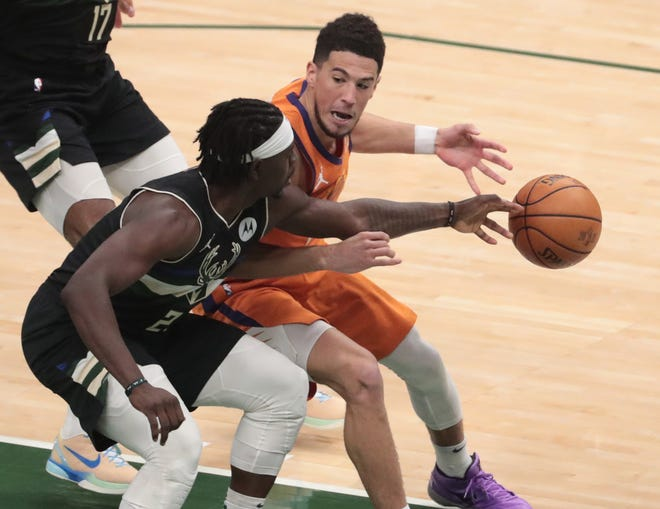 Phoenix Suns guard Devin Booker (1) has the ball deflected away by Milwaukee Bucks guard Jrue Holiday (21) during Game 6 of the NBA Finals at Fiserv Forum July 20, 2021.
