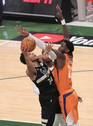 Milwaukee Bucks forward Giannis Antetokounmpo (34) is fouled by Phoenix Suns center Deandre Ayton (22) during Game 6 of the NBA Finals at Fiserv Forum July 20, 2021.