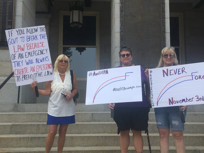 Hanover residents Edie Springfloat, Sheila O'Neill and Christie Rutledge pose with signs outside of the York County Administrative Center. The three attended the Board of Commissioners meeting in support of a forensic election audit of the 2020 election.
