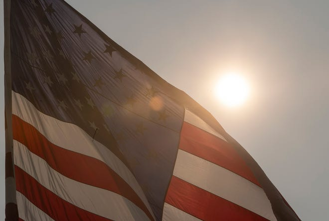 A flag at York Water Company's Reservoir Park dances behind a hazy, golden orb. Smoke from massive wildfires on the western side of the continent have reached high into the  atmosphere and are being carried thousands of miles east by high-level winds.