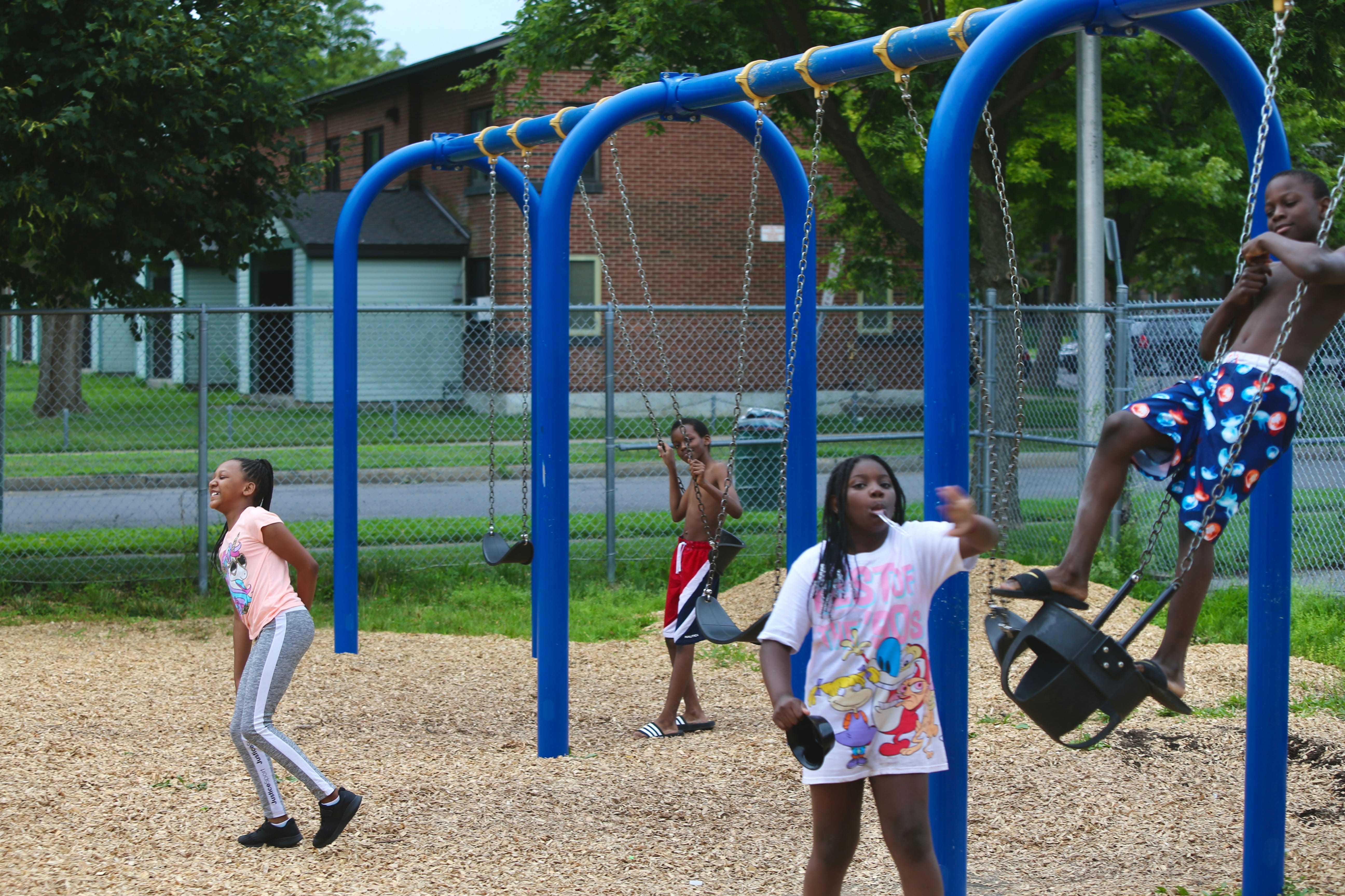 Children play and pose for the camera at playground close to I-81 in Pioneer Homes on July 16.