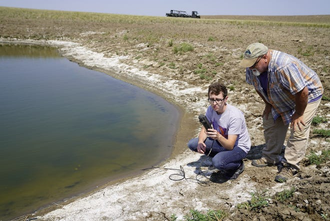 An undergraduate researcher, left, and Patrick Kozak, right, test a stock dam in northwestern South Dakota. Ongoing research at School of Mines shows that salinity levels in stock dams are higher this year due to drought conditions.