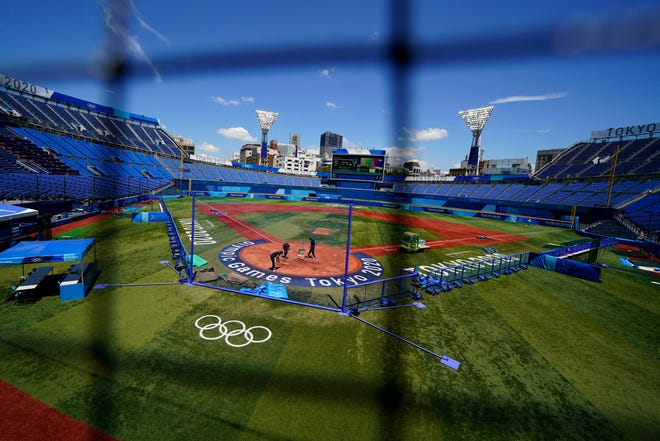 Workers prepare the field at Yokohama Baseball Stadium in preparation for softball competition at the 2020 Summer Olympics, Wednesday, July 21, 2021, in Yokohama, Japan.