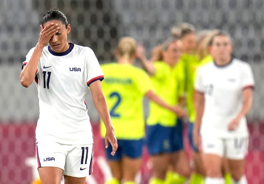 United States' Christen Press reacts as Sweden's players celebrate their third goal during a women's soccer match at the 2020 Summer Olympics, Wednesday, July 21, 2021, in Tokyo, Japan.