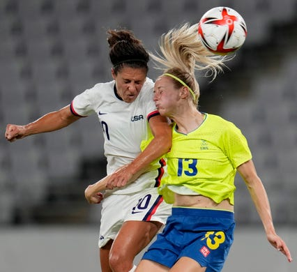 United States' Carli Lloyd, left, and Sweden's Amanda Ilestedt, right, go for a header during a women's soccer match at the 2020 Summer Olympics on Wednesday, July 21, 2021, in Tokyo, Japan.