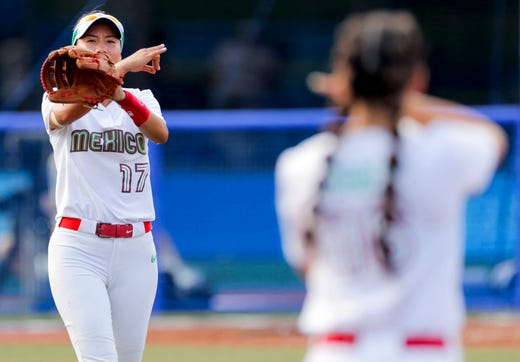 Mexico's shortstop Anissa Urtez (L) gestures at outfielder Tatyana Forbes (R) on July 21, 2021, during the 4th inning of the Tokyo 2020 Olympic Games softball opening round game between Mexico and Canada at Fukushima Azuma Baseball Stadium in Fukushima, Japan.