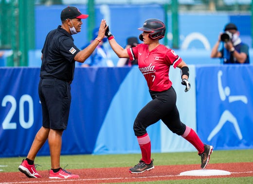Canada's Jenn Salling is congratulated by head coach Mark Smith after scoring a home run during the softball game between Mexico and Canada during the Tokyo 2020 Olympic Summer Games held at Fukushima Azuma Stadium in Fukushima, Japan.