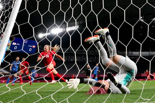 Japan's goalkeeper Sakiko Ikeda falls as Canada's players celebrate after Canada's Christine Sinclair scores a goal against Japan during a women's soccer match at the 2020 Summer Olympics, Wednesday, July 21, 2021, in Sapporo, Japan. (AP Photo/Silvia Izquierdo) ORG XMIT: OLYKS318