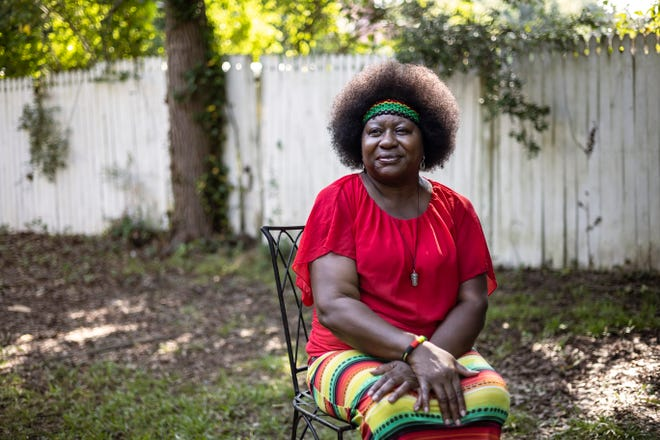 """Angela Phinazee, 55, who has been a spoken-word artist since since age 11, sits for a portrait in her backyard on Thursday, July 22, 2021, in Athens. Phinazee earned her stage name """"Angela the Arsonist"""" after finishing a performance in her 30s when an attendee praised that """"she really burned the stage down."""""""